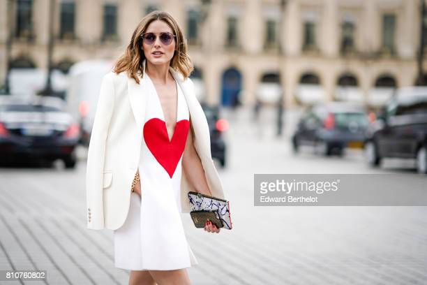 Olivia Palermo wears a white blazer jacket a white low neck dress with a printed red heart a clutch black and white shoes at Place Vendome outside...