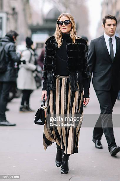Olivia Palermo wears black sunglasses a black fur coat a striped dress and black heels outside the Elie Saab show during Paris Fashion Week Haute...