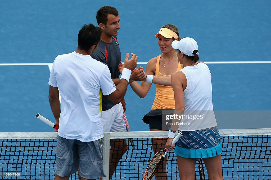 Olivia Rogowska (2R) of Australia, Marinko Matosevic (2L) of Australia shake hands with Katarina Srebotnik of Slovenia and Nenad Zimonjic of Serbia in their first round mixed doubles match during day five of the 2013 Australian Open at Melbourne Park on January 18, 2013 in Melbourne, Australia.