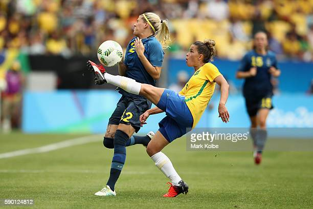 Olivia Schough of Sweden is tackled during the Women's Football Semi Final between Brazil and Sweden on Day 11 of the Rio 2016 Olympic Games at...