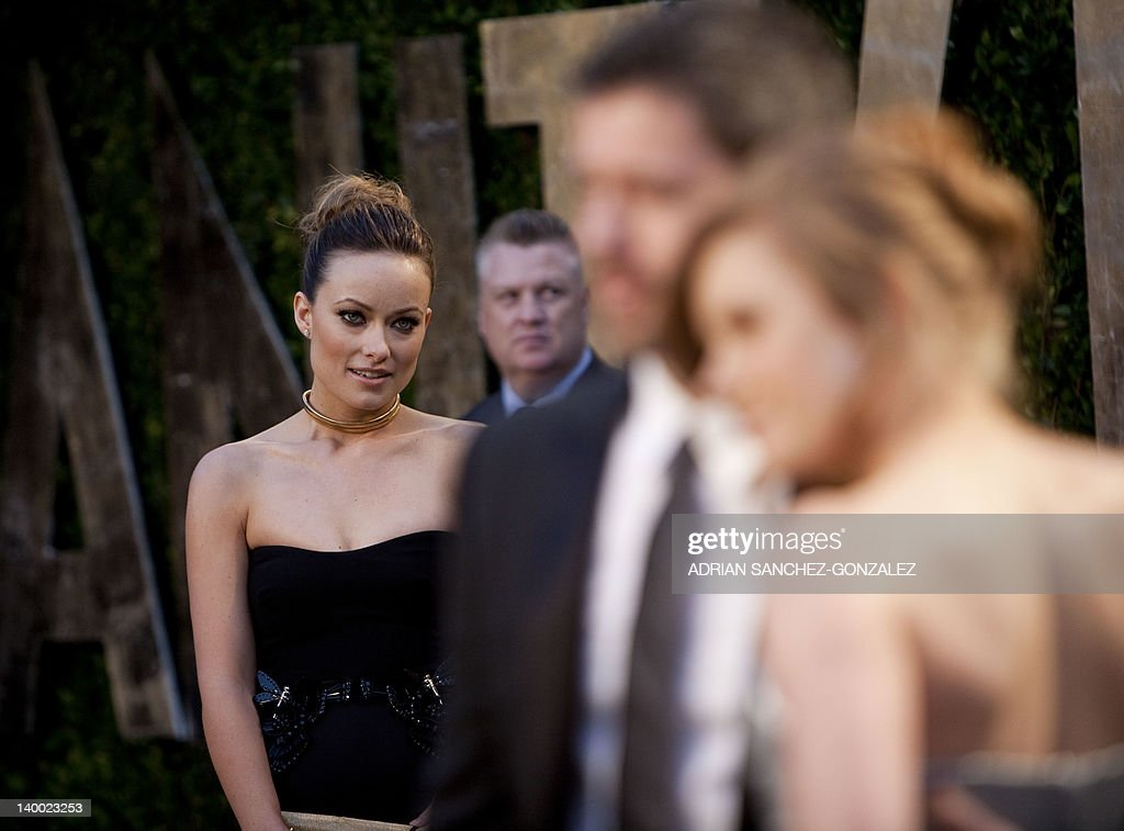 Olivia Wilde (L) watches as Amy Adams and husband Darren Le Gallo pose for pictures as they arrive at the Vanity Fair Oscar Party, for the 84th Annual Academy Awards, at the Sunset Tower on February 26, 2012 in West Hollywood, California.