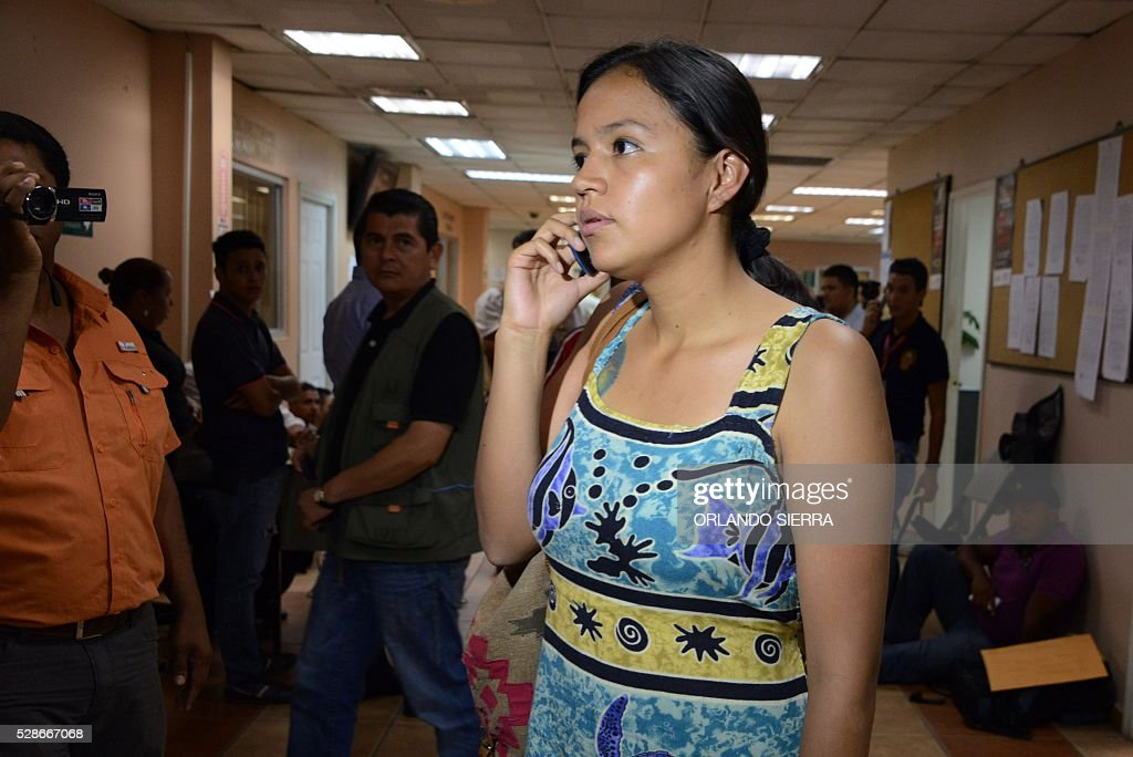 Olivia Zuniga Caceres, daughter of Honduran indigenous leader Berta Caceres, speaks on her mobile phone at court in Tegucigalpa on May 6, 2016. A judge ordered Tuesday the preventive detention of four suspects of the killing of Berta Caceres. / AFP / ORLANDO