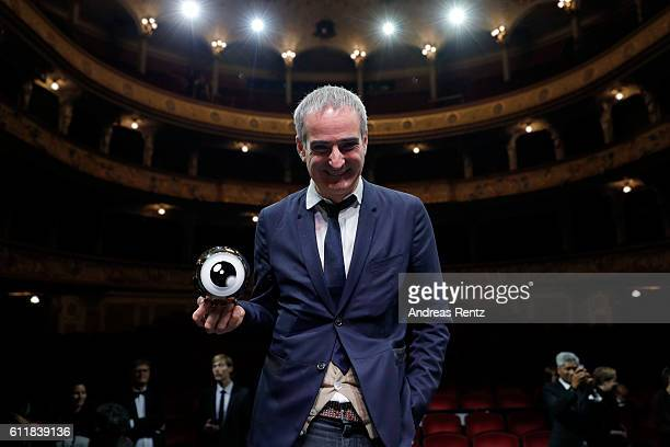 Olivier Assayas poses with his 'Tribute to' award on stage during the Award Night Ceremony during the 12th Zurich Film Festival on October 1 2016 in...