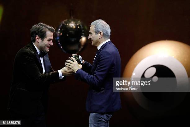 Olivier Assayas receives the 'Tribute to' award from Festival director Karl Spoerri on stage during the Award Night Ceremony during the 12th Zurich...