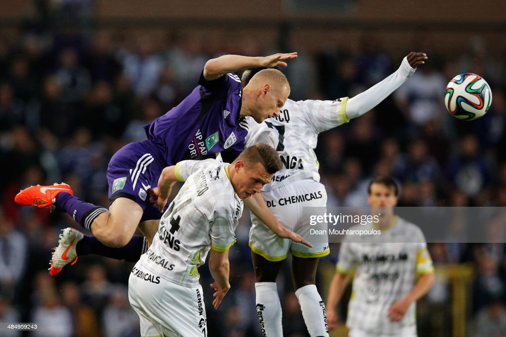 Olivier Deschacht of Anderlecht and Jens Naessens and Fabrice Olinga of Zulte battle for the header during the Jupiler Pro League match between RSC...