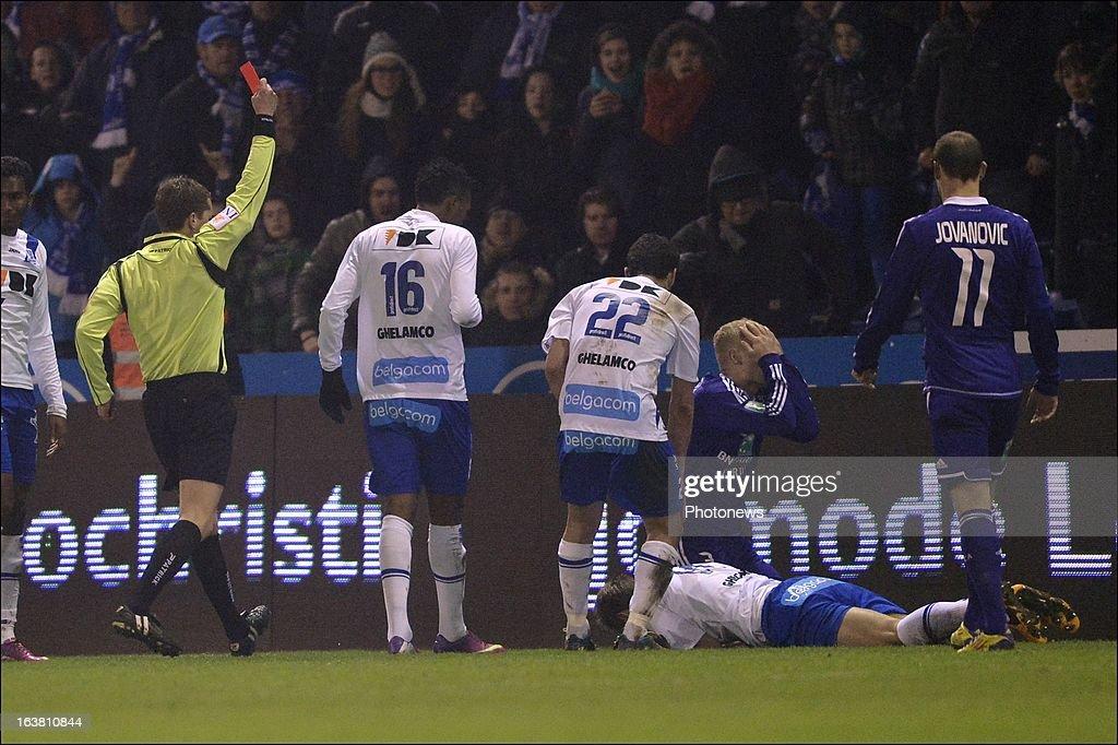 Olivier Deschacht of RSC Anderlecht is shown a red card by referee Jonathan Lardot during the Jupiler League match between KAA Gent and RSC Anderlecht on March 16, 2013 in the Otten stadium Gent, Belgium.