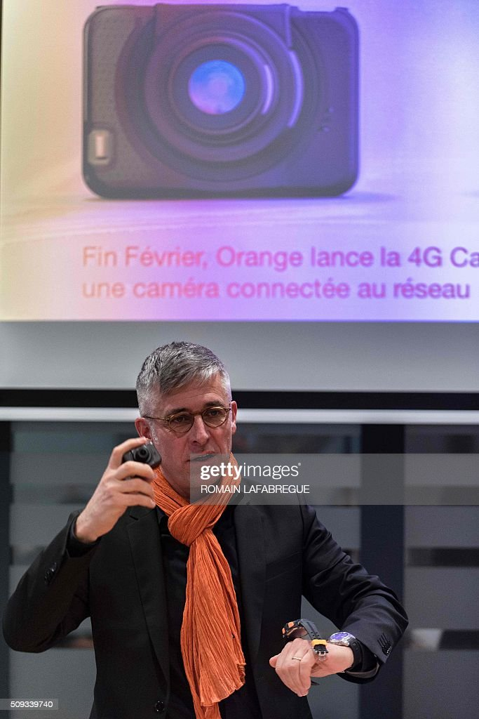 Olivier Faure, director of French telecommunications corporation Orange's East Center, displays a new connected camera during a press conference at Orange's mobile phone supervision center in Lyon on February 10, 2016. / AFP / ROMAIN LAFABREGUE