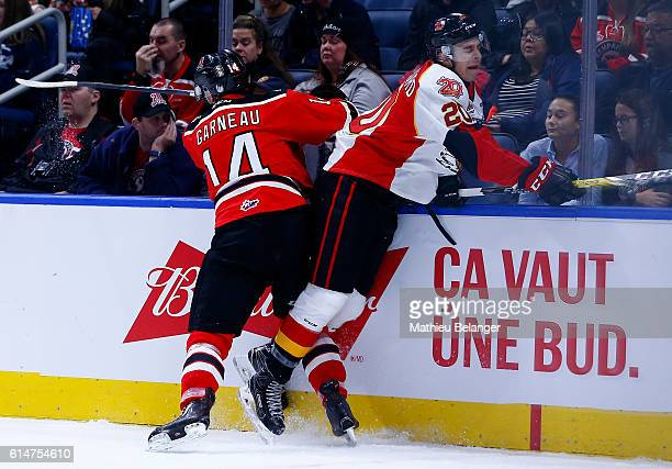 Olivier Garneau of the Quebec Remparts hits Xavier Bouchard of the Baie Comeau Drakkar during their QMJHL hockey game at the Centre Videotron on...