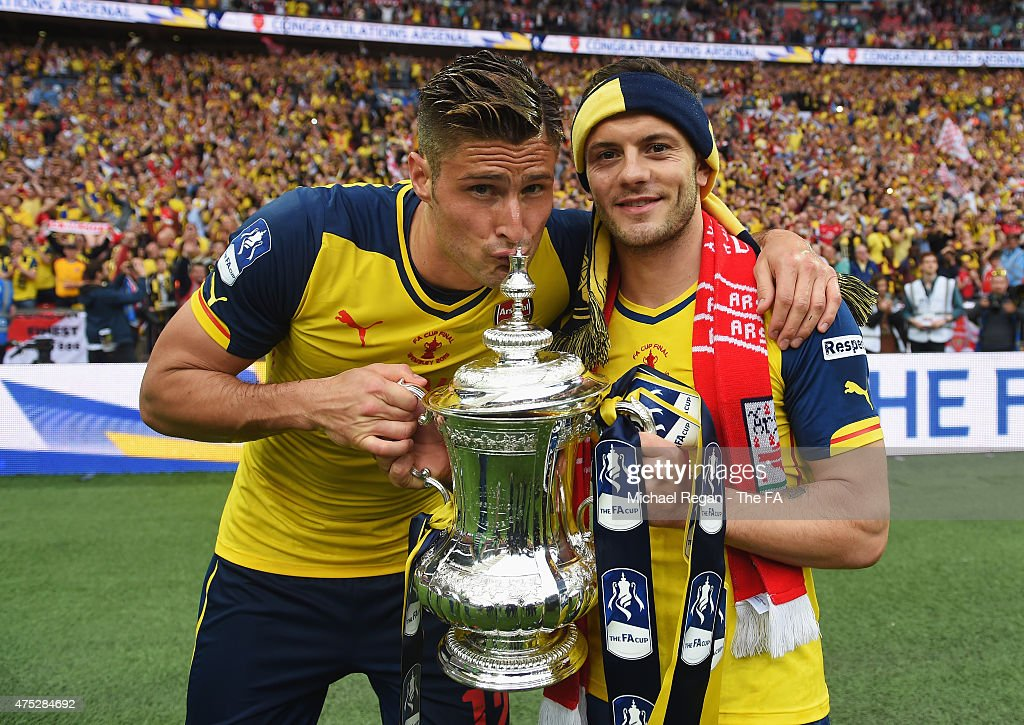 Olivier Giroud and Jack Wilshere of Arsenal celebrate on the pitch with the trophy after winning the FA Cup Final between Aston Villa and Arsenal at...