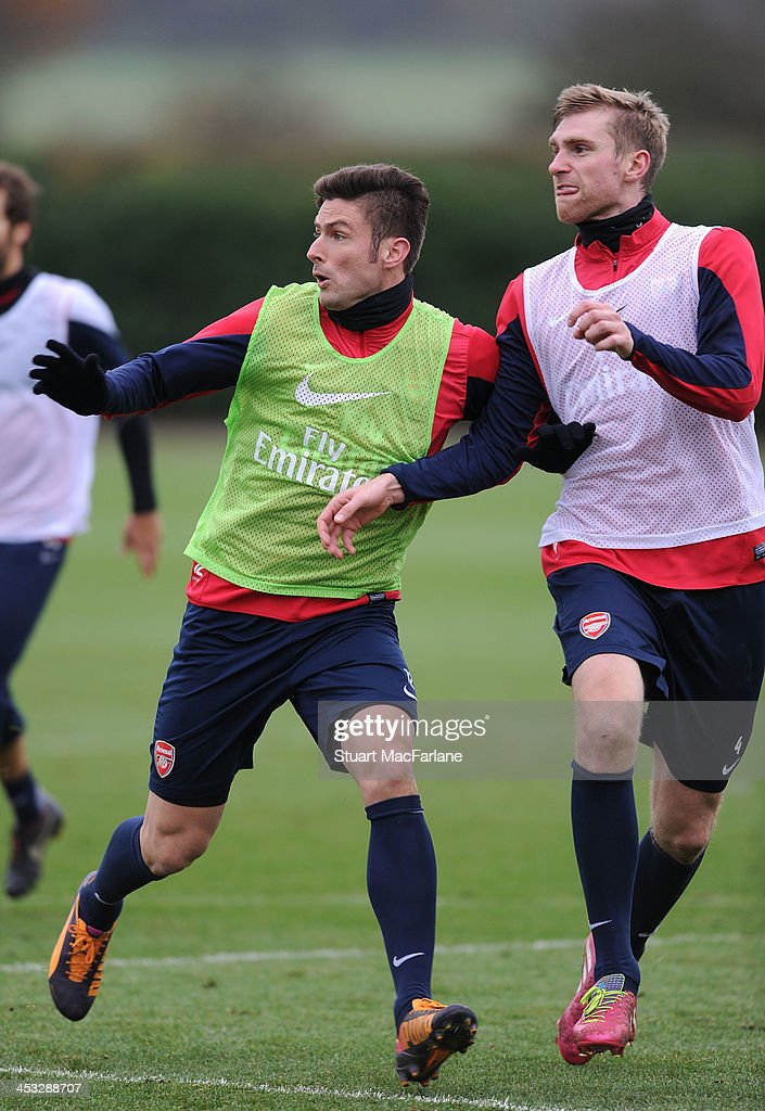 Olivier Giroud and Per Mertesacker of Arsenal in action during a training session at London Colney on December 3, 2013 in St Albans, England.