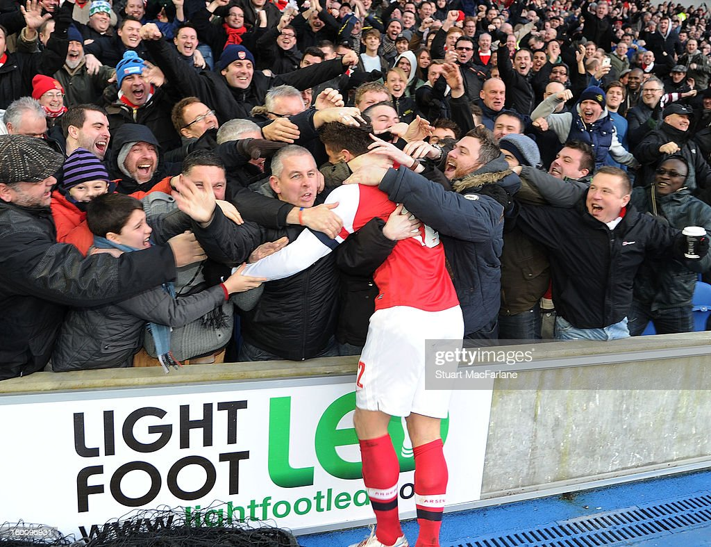 Olivier Giroud celebrates scoring the 2nd goal with the Arsenal fans during the FA Cup Fourth Round match between Brighton & Hove Albion and Arsenal at the Amex Stadium on January 26, 2013 in Brighton, England.