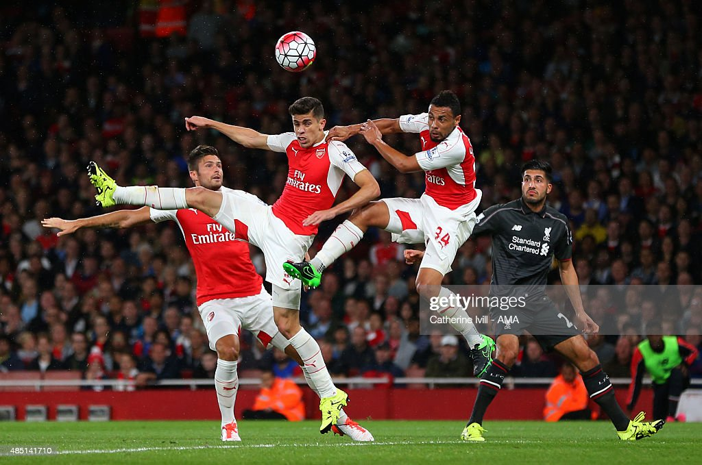 Olivier Giroud, Gabriel Paulista and Francis Coquelin of Arsenal vie for the ball as Emre Can of Liverpool looks on during the Barclays Premier League match between Arsenal and Liverpool at the Emirates Stadium on August 24, 2015 in London, United Kingdom.