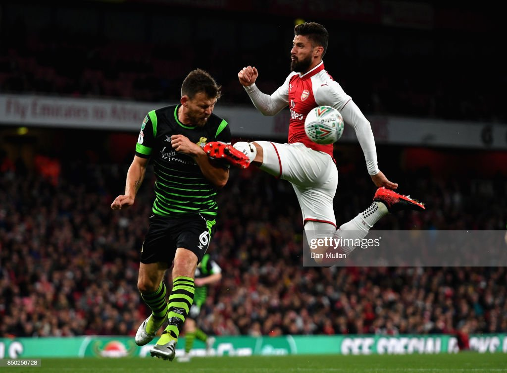 Olivier Giroud of Arsenal and Andy Butler of Doncaster Rovers battle for possession during the Carabao Cup Third Round match between Arsenal and Doncaster Rovers at Emirates Stadium on September 20, 2017 in London, England.