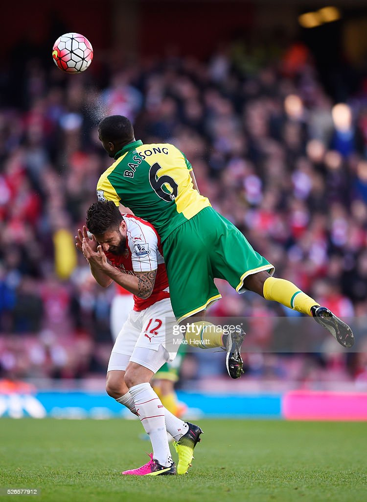 Olivier Giroud of Arsenal and Sebastien Bassong of Norwich City compete for the ball during the Barclays Premier League match between Arsenal and...