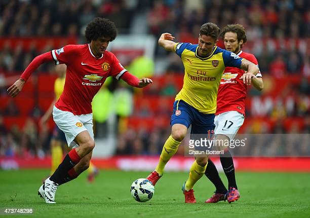 Olivier Giroud of Arsenal battles with Marouane Fellaini and Daley Blind of Manchester United during the Barclays Premier League match between...
