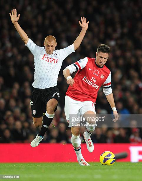 Olivier Giroud of Arsenal breaks past Steve Sidwell of Fulham during the Barclays Premier League match between Arsenal and Fulham at Emirates Stadium...