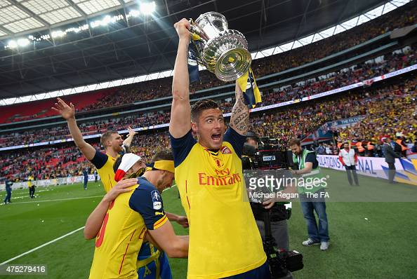 Olivier Giroud of Arsenal celebrates on the pitch with the trophy after winning the FA Cup Final between Aston Villa and Arsenal at Wembley Stadium...