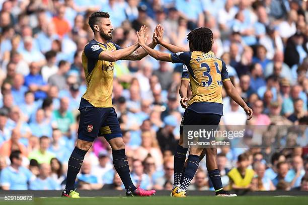 Olivier Giroud of Arsenal celebrates scoring his side's first goal with Mohamed Elneny of Arsenal during the Barclays Premier League match between...