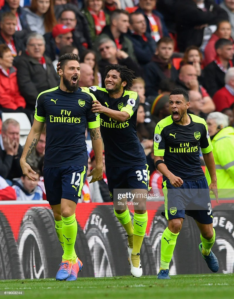 Olivier Giroud of Arsenal (L) celebrates scoring his sides second goal with his Arsenal team mates Mohamed Elneny (c) and Francis Coquelin during the Premier League match between Sunderland and Arsenal at the Stadium of Light on October 29, 2016 in Sunderland, England.