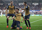 Olivier Giroud of Arsenal celebrates scoring his team's first goal with his team mates Per Mertesacker and Mesut Ozil during the Barclays Premier...