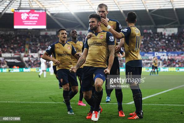 Olivier Giroud of Arsenal celebrates scoring his team's first goal with his team mates during the Barclays Premier League match between Swansea City...