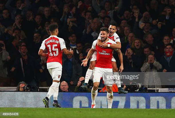 Olivier Giroud of Arsenal celebrates with Alex OxladeChamberlain and Alexis Sanchez as he scores their first goal during the UEFA Champions League...