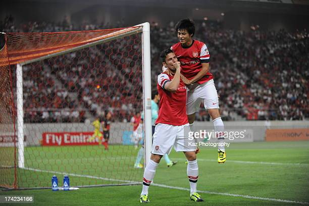 Olivier Giroud of Arsenal celebrates with Ryo Miyaichi of Arsenal after his opener during the preseason friendly match between Nagoya Grampus and...