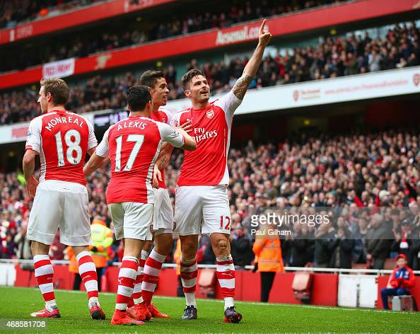 Olivier Giroud of Arsenal celebrates with team mates after scoring his team's fourth goal during the Barclays Premier League match between Arsenal...