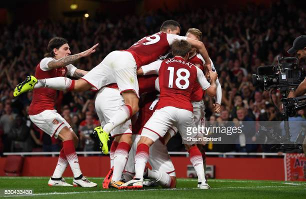 Olivier Giroud of Arsenal celebrates with teammates after scoring his team's fourth goal during the Premier League match between Arsenal and...