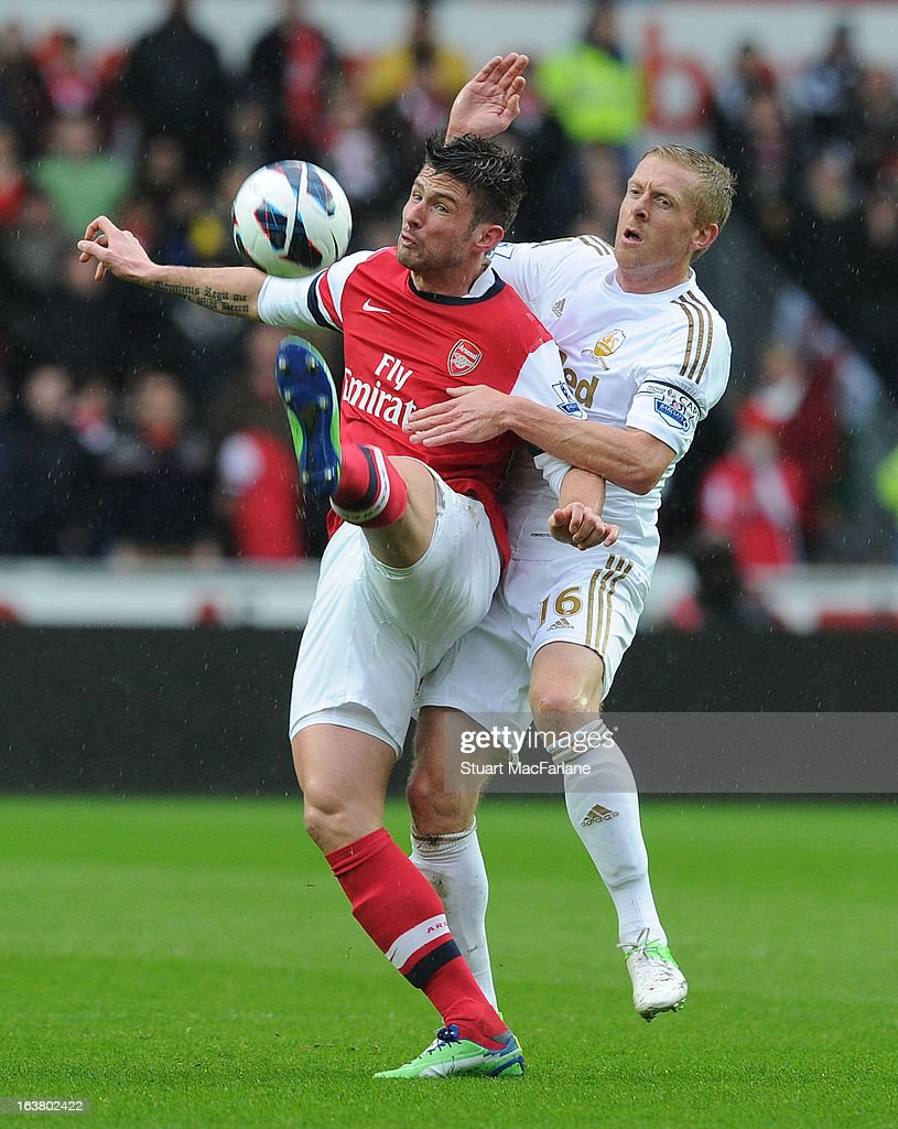 Olivier Giroud of Arsenal challenged by Garry Monk of Swansea during the Premier League match between Swansea City and Arsenal at Liberty Stadium on March 16, 2013 in Swansea, Wales.