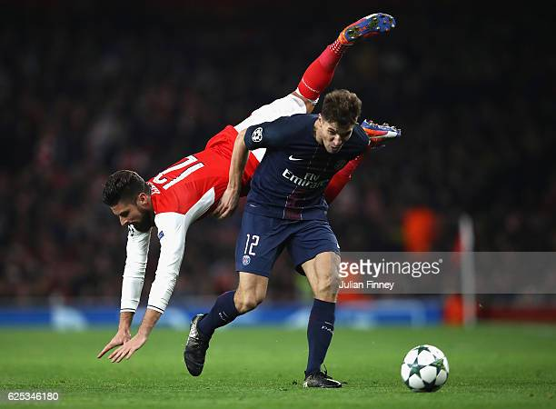 Olivier Giroud of Arsenal flys over Thomas Meunier of PSG during the UEFA Champions League Group A match between Arsenal FC and Paris SaintGermain at...