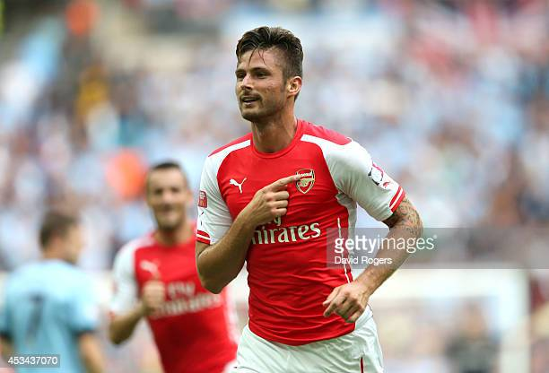 Olivier Giroud of Arsenal gestures to the badge on his shirt after scoring the third goal during the FA Community Shield match between Manchester...