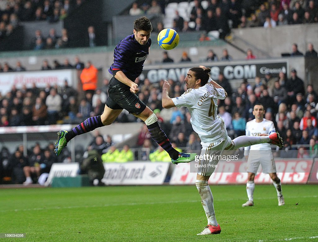 Olivier Giroud of Arsenal heads the ball wide under pressure from Chico Flores of Swansea during the FA Cup Third Round match between Swansea City and Arsenal at the Liberty Stadium on January 6, 2013 in Swansea, Wales.