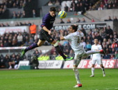 Olivier Giroud of Arsenal heads the ball wide under pressure from Chico Flores of Swansea during the FA Cup Third Round match between Swansea City...