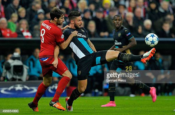Olivier Giroud of Arsenal holds off Javi Martinez of Bayern Muenchen during the UEFA Champions League Group F match between FC Bayern Muenchen and...