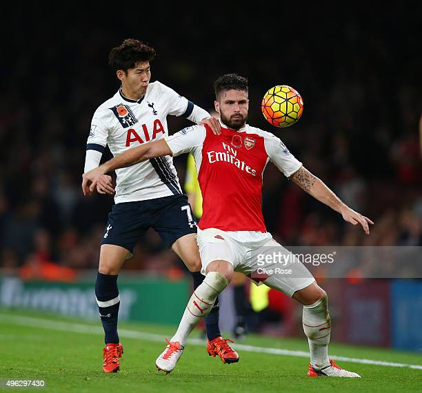 Olivier Giroud of Arsenal holds off Son HeungMin of Spurs during the Barclays Premier League match between Arsenal and Tottenham Hotspur at the...