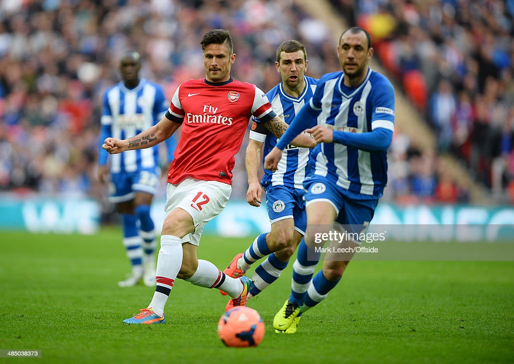Olivier Giroud of Arsenal in action with Ivan Ramis and James McArthur of Wigan Athletic during the FA Cup SemiFinal match between Wigan Athletic and...