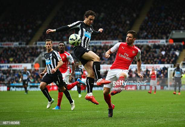 Olivier Giroud of Arsenal is challenged by Daryl Janmaat of Newcastle United during the Barclays Premier League match between Newcastle United and...