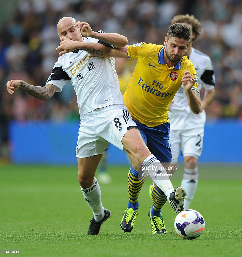 <a gi-track='captionPersonalityLinkClicked' href=/galleries/search?phrase=Olivier+Giroud&family=editorial&specificpeople=5678034 ng-click='$event.stopPropagation()'>Olivier Giroud</a> of Arsenal is challenged by <a gi-track='captionPersonalityLinkClicked' href=/galleries/search?phrase=Jonjo+Shelvey&family=editorial&specificpeople=4940315 ng-click='$event.stopPropagation()'>Jonjo Shelvey</a> of Swansea during the Barclays Premier League match between Swansea and Arsenal at Liberty Stadium on September 28, 2013 in Swansea, Wales.