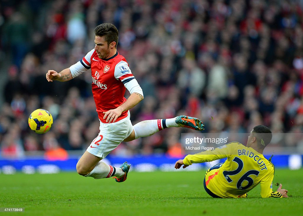 Olivier Giroud of Arsenal (L) is challenged by Liam Bridcutt of Sunderland during the Barclays Premier League match between Arsenal and Sunderland at Emirates Stadium on February 22, 2014 in London, England.