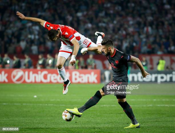 Olivier Giroud of Arsenal is challenged by Vujadin Savic of Crvena Zvezda during the UEFA Europa League group H match between Crvena Zvezda and...