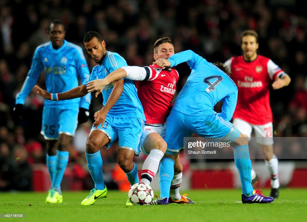 Olivier Giroud of Arsenal is closed down by Alaixys Romao and Lucas Mendes of Marseille during the UEFA Champions League Group F match between Arsenal and Olympique de Marseille at Emirates Stadium on November 26, 2013 in London, England.