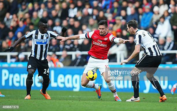 Olivier Giroud of Arsenal is closed down by Cheick Tiote and Michael Williamson of Newcastle United during the Barclays Premier League match between...