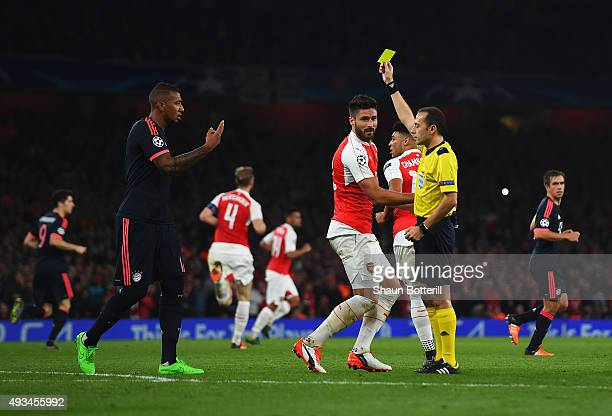 Olivier Giroud of Arsenal is shown a yellow card by referee Cuneyt Cakir during the UEFA Champions League Group F match between Arsenal FC and FC...