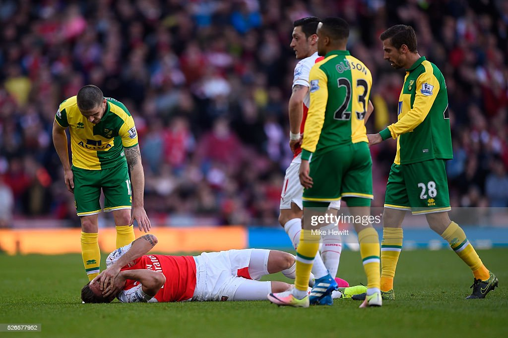 Olivier Giroud of Arsenal lies on the pitch after colliding with Sebastien Bassong of Norwich City during the Barclays Premier League match between Arsenal and Norwich City at The Emirates Stadium on April 30, 2016 in London, England