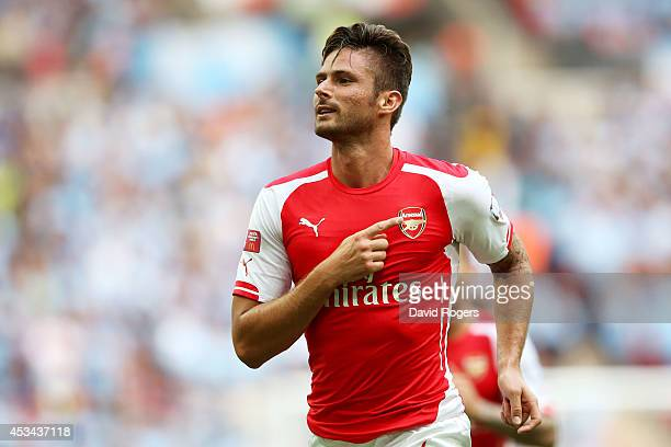 Olivier Giroud of Arsenal points to the badge on his shirt as he celebrates scoring the third goal during the FA Community Shield match between...