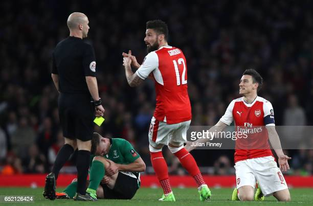 Olivier Giroud of Arsenal reacts as referee Anthony Taylor shows a yellow card to Laurent Koscielny of Arsenal for a foul on Jack Muldoon of Lincoln...