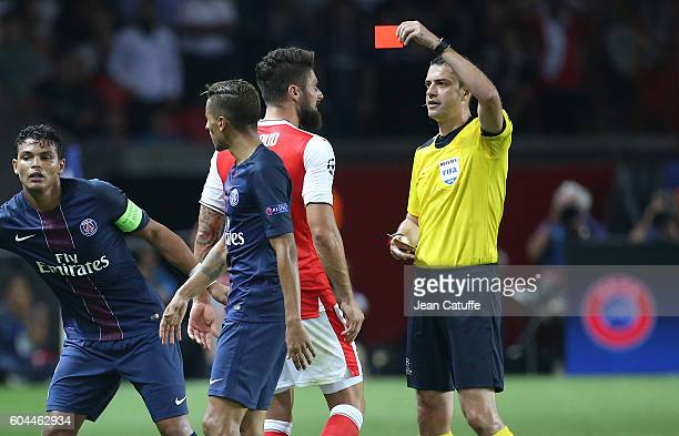 Olivier Giroud of Arsenal receives a red card from referee Viktor Kassai of Hungary during the UEFA Champions League group phase match between Paris...