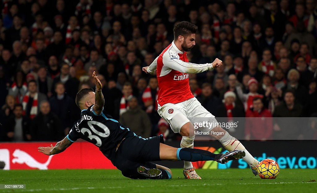 Olivier Giroud of Arsenal scores his side's second goal past Nicolas Otamendi of Manchester City during the Barclays Premier League match between Arsenal and Manchester City at Emirates Stadium on December 21, 2015 in London, England.