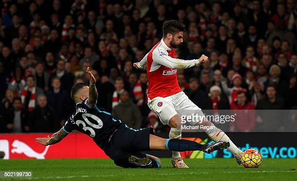 Olivier Giroud of Arsenal scores his side's second goal past Nicolas Otamendi of Manchester City during the Barclays Premier League match between...